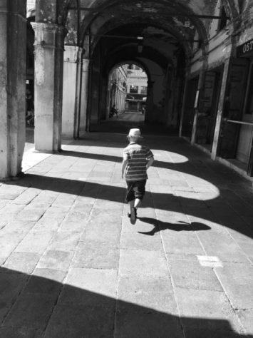 A young boy runs along a Venice street