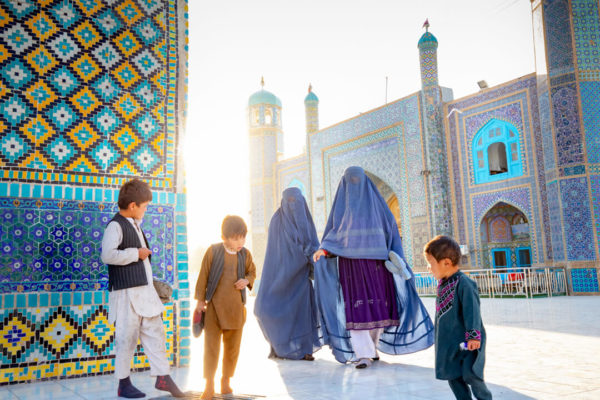 Women and children in traditional Islamic dress stand before a mosque.