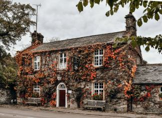 a british village house covered in foliage
