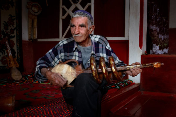 old man holding traditional tajik instrument