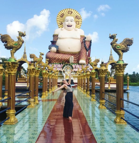 woman on ornate pier with buddha statue