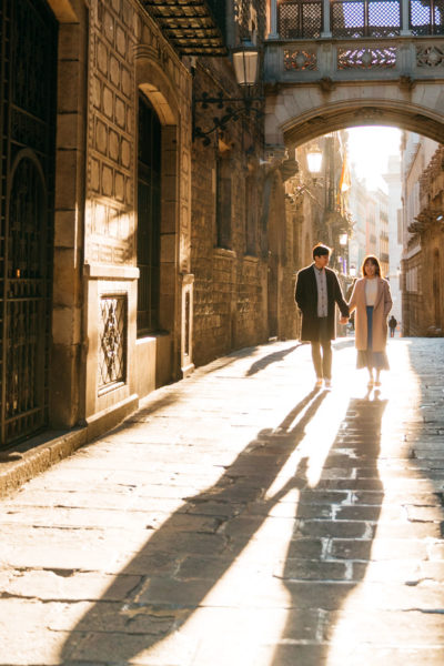 couple holding hands in sunny alleyway