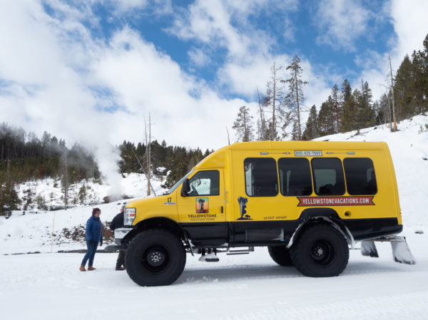 a yellow snow coach during winter in yellowstone