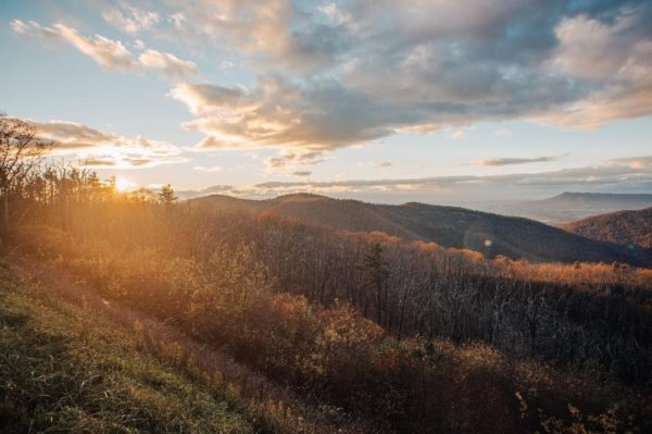 sun setting on rolling hills