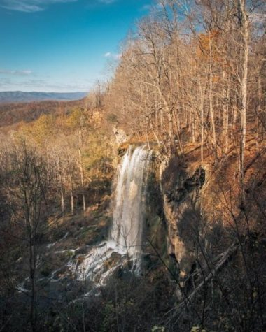 waterfall with sunny hilly backdrop
