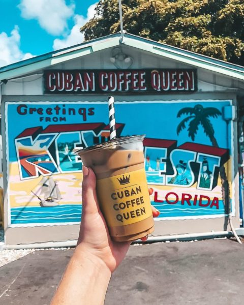 hand holding coffee in front of florida keys mural