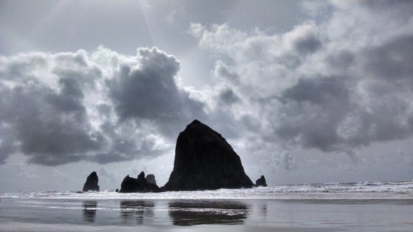 Haystack Rock on a partly cloudy day.
