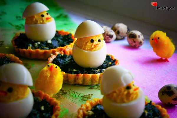 Hard-boiled eggs cut and refilled with egg yolk mixture, styled in a form of a chick. Each chick deviled egg is standing on a small spinach tartelettes. Small deco chicks and small eggs in the background.