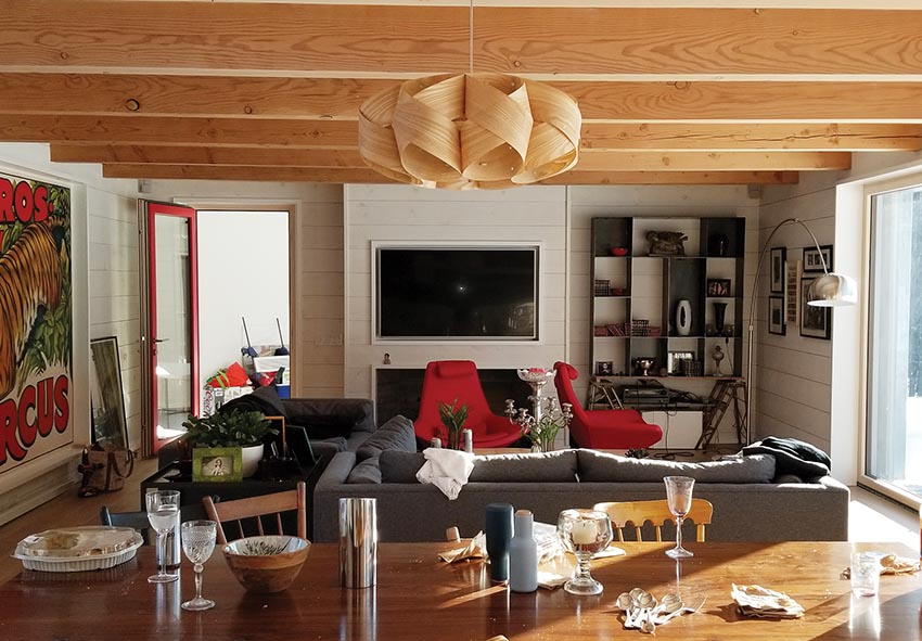 Daytime interior of a living room and dining area in a Passive House. Visible are a wood dining table, a sofa and chairs, under exposed wood beams.
