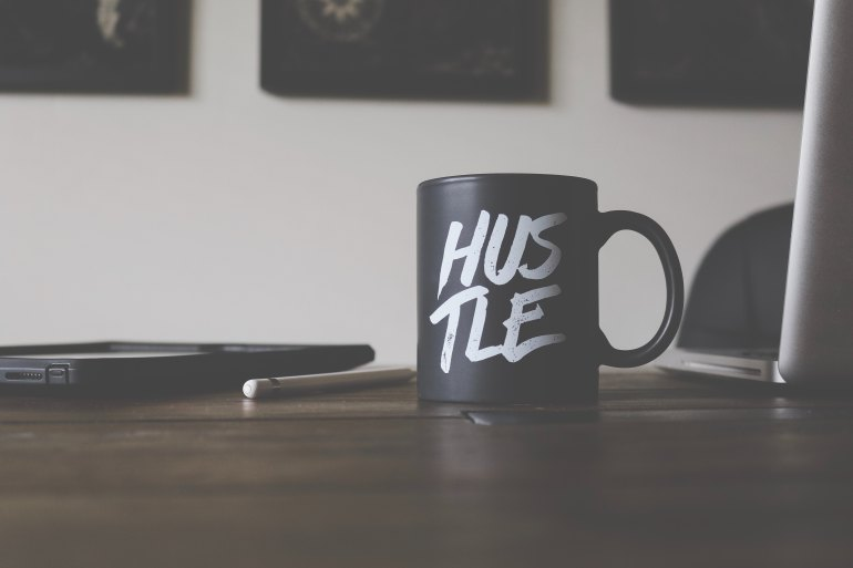 black and white Hustle-printed ceramic mug on table