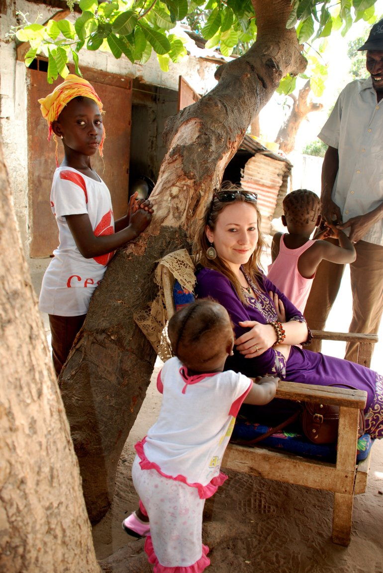 Woman sitting down in a chair by a tree surrounded by a local family in The Gambia, West Africa
