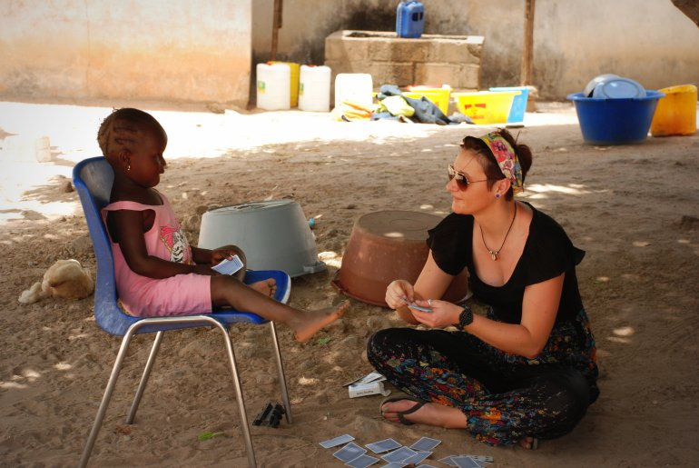A girl sits on the floor while playing cards with a young child in The Gambia, West Africa