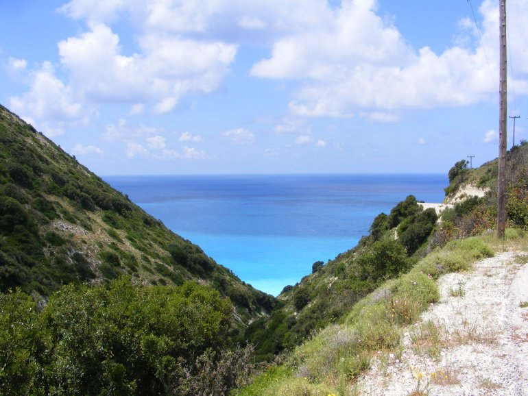 Looking through a green valley out to a beautiful turquoise ocean at Myrtos Beach in Kefalonia