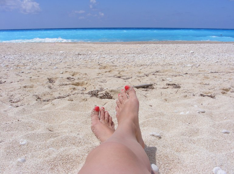 A ladies feet with painted red toe nails on a beach in Kefalonia, Greece, looking out to a vivid turquoise ocean