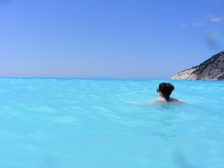 A woman swims in vivid turquoise water at Myrtos Beach in Kefalonia