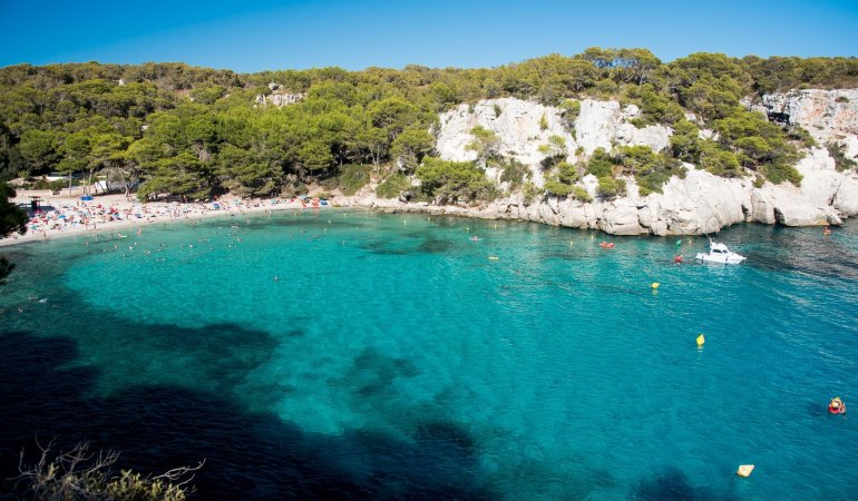 Turquoise sea and white cliffs at Cala Macarella in Menorca