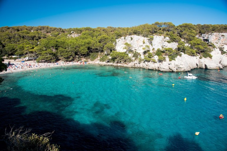 Beautiful turquoise sea framed by white cliffs at Cala Macarella in Menorca