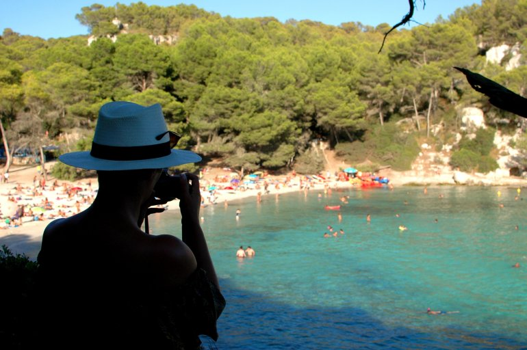 Girl wearing white hat overlooking busy beach at Cala Macarella in Menorca