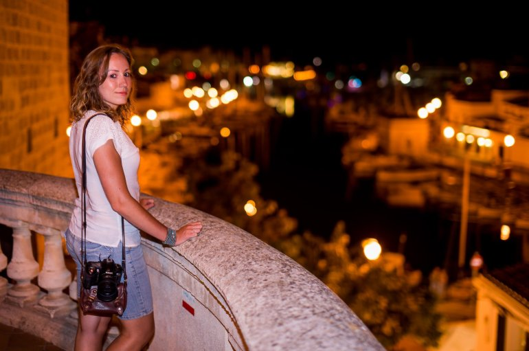 Girl looks over twinkling lights of Menorca Ciutadella and Harbour