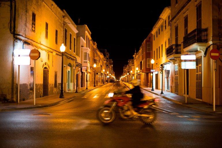 Motorbike whizzes past beautiful street in Menorca's Ciutadella at night