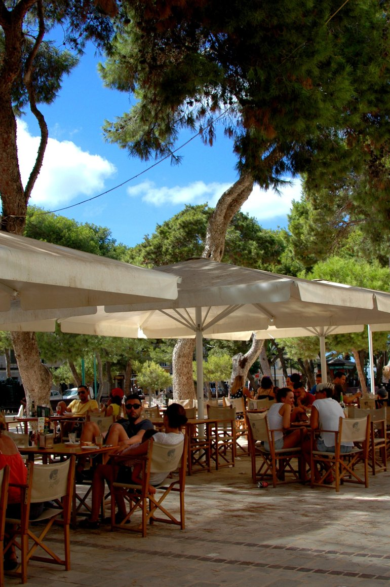 Locals and tourists enjoy drinks and lunch at outside restaurant in Cuitadella Menorca