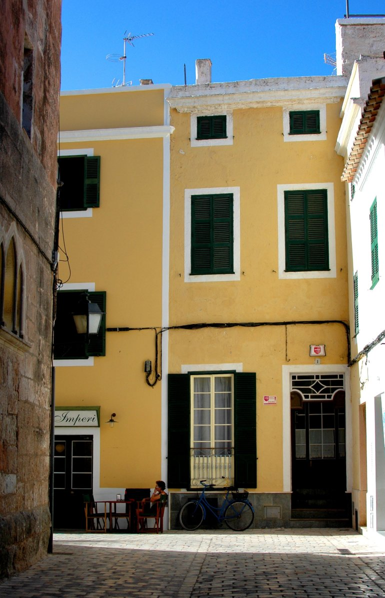 Lady sits at table in quiet street in front of bright yellow building in Menorca Spain