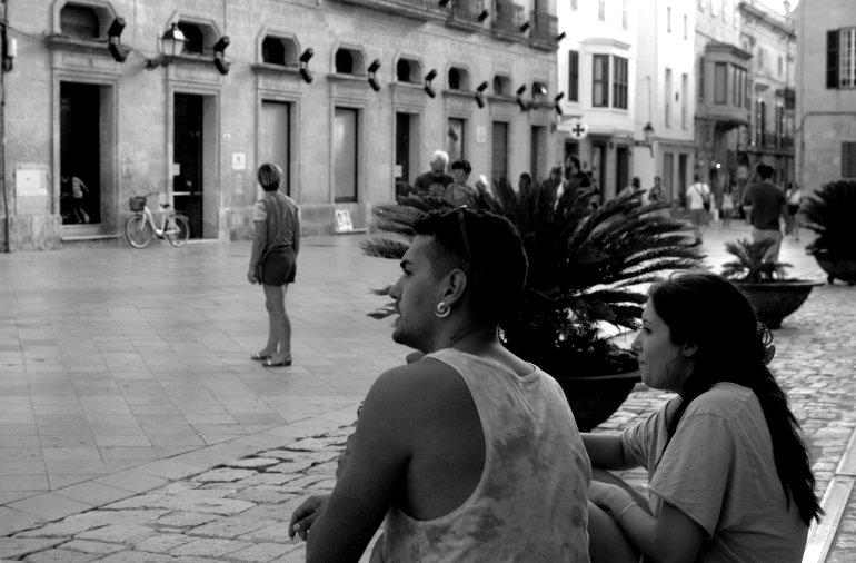 Locals sit on bench in street in Menorca's Ciutadella