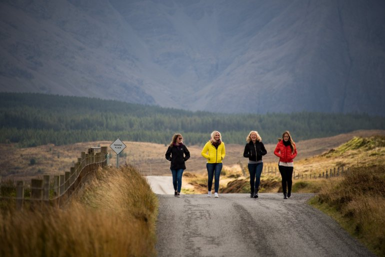 Four women walk along a scenic road on the Isle of Skye in Scotland