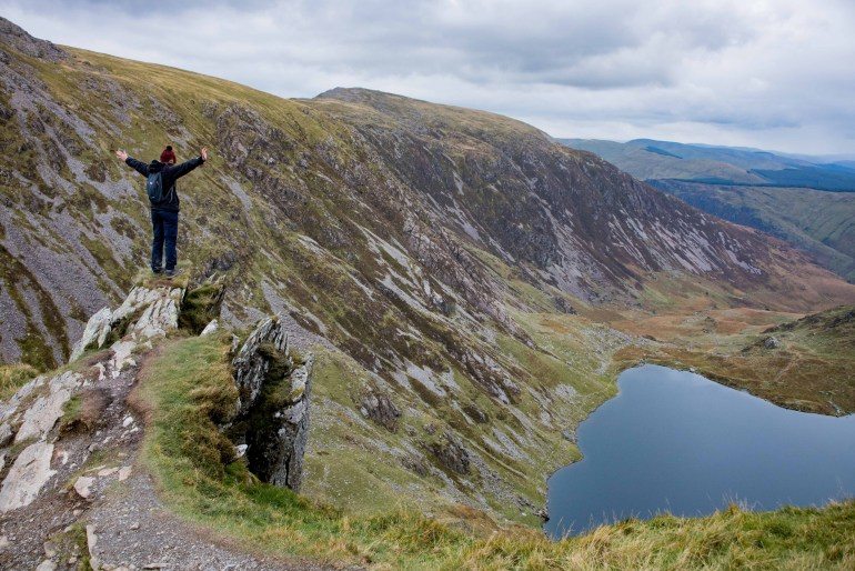 Girl stands on edge of cliff at the top of Cadair Idris over looking a lake in Snowdonia National Park