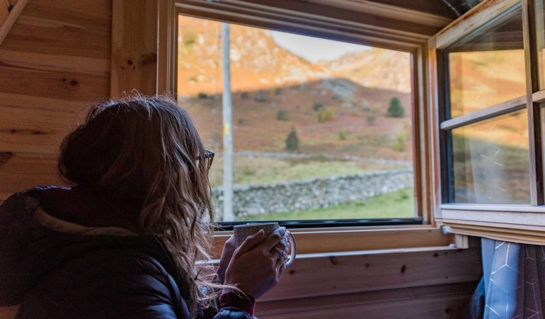 Girl looks out of a wooden cabin window at a view of mountains in Snowdonia while holding a hot cup of coffee