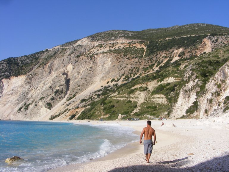 A man walks along the beach with waves lapping against the shore at Myrtos Beach in Kefalonia, Greece