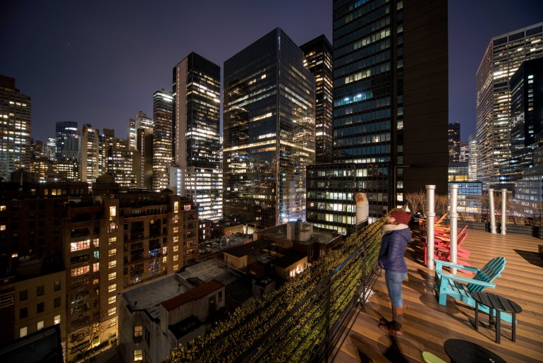 Girl looks out on New York skyline from Pod 51 Hotel rooftop terrace