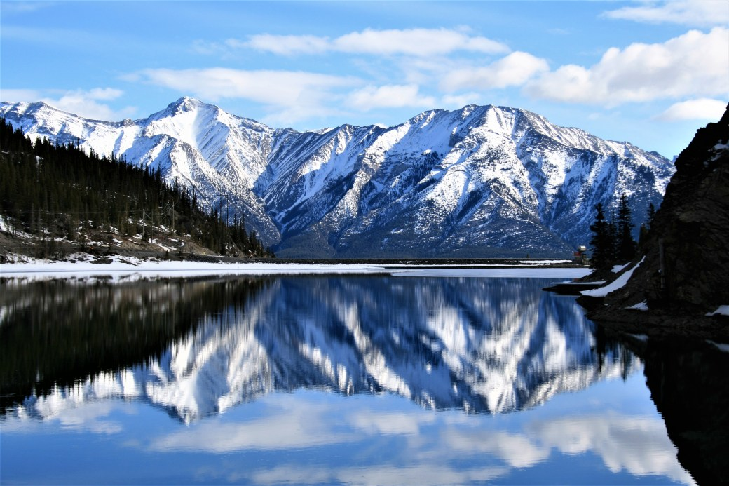 A perfect reflection lies between Canmore and the entrance to Spray Valley Provincial Park