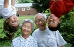Two Asian-American kids hang upside down beside their grandparents.