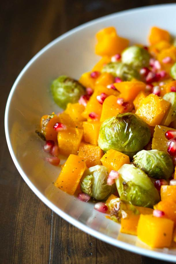Fall Roasted Vegetables | Roasted butternut squash, brussels sprouts, sprinkled with pomegranate arils | Easy Vegan Side Dish | https://passtheplants.com