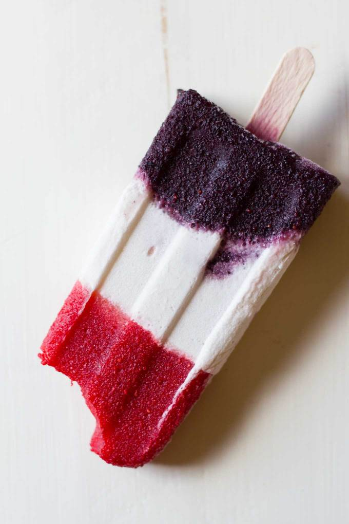 Dairy-Free Patriotic Popsicles | Red, white, and blue layered popsicle with bite taken out | Vegan, dairy-free, naturally sweetened, fruit dessert, 4th of July, Memorial Day, popsicle | https://passtheplants.com/