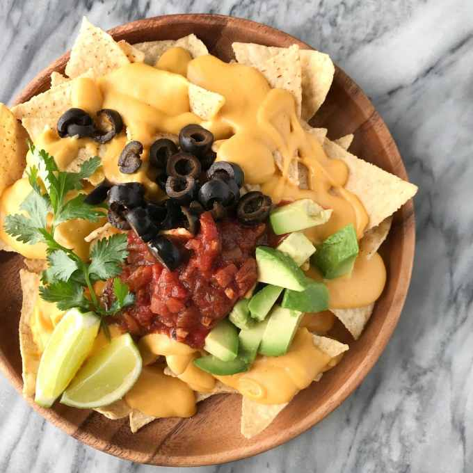 Protein-Packed Vegan Cheese Sauce   Plate of nachos with vegan cheese sauce   Whole foods plant based   Oil-free   #plantbased #vegan #oilfree #wfbp   https://passtheplants.com/