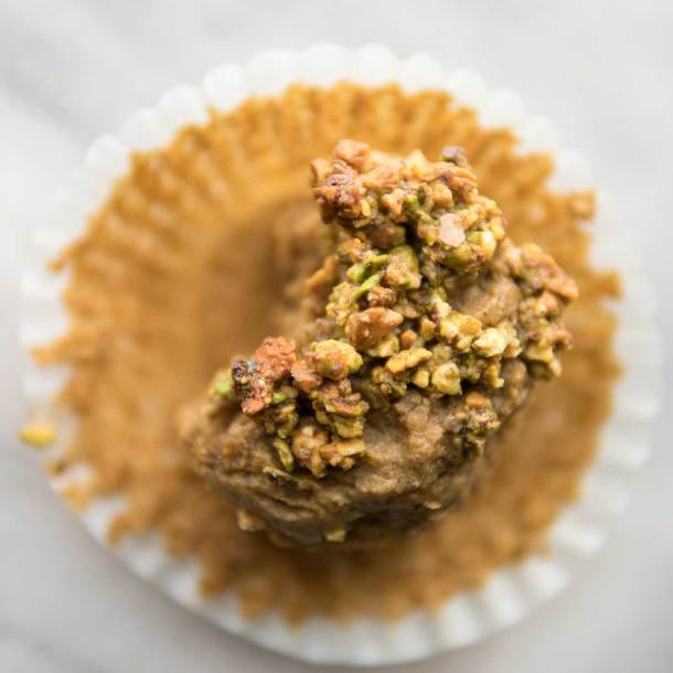 overhead image of pistachio cardamom blender muffin with a bite taken out