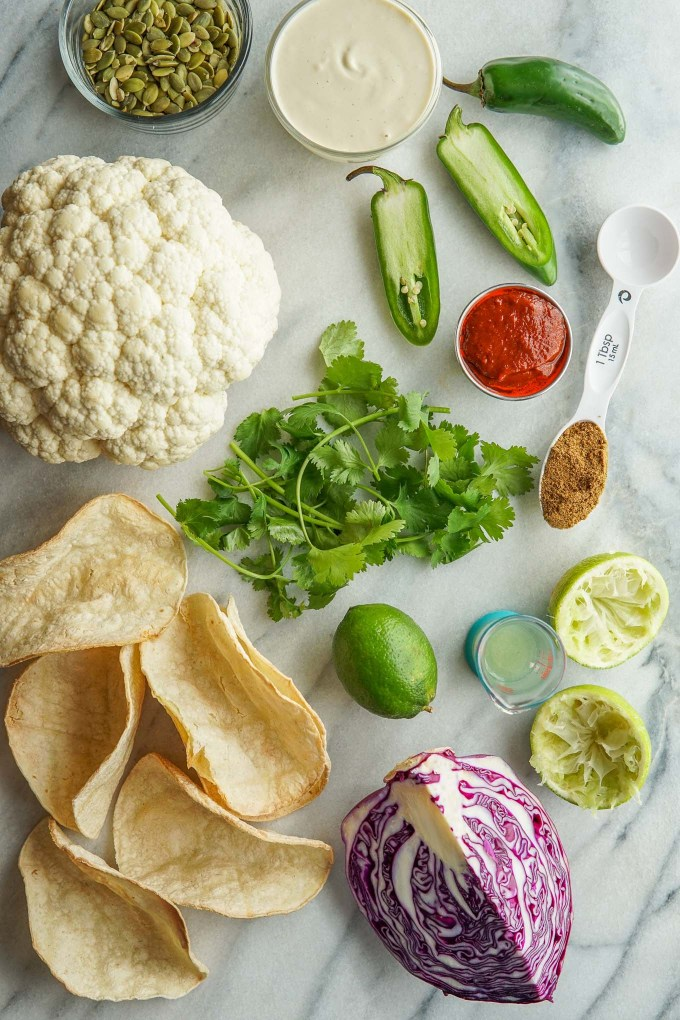 Overhead image of ingredients for Chipotle Cauliflower Tacos - cauliflower, pepitas, cashew cream, jalapeño, chipotle puree, ground cumin, lime, corn tortillas, purple cabbage