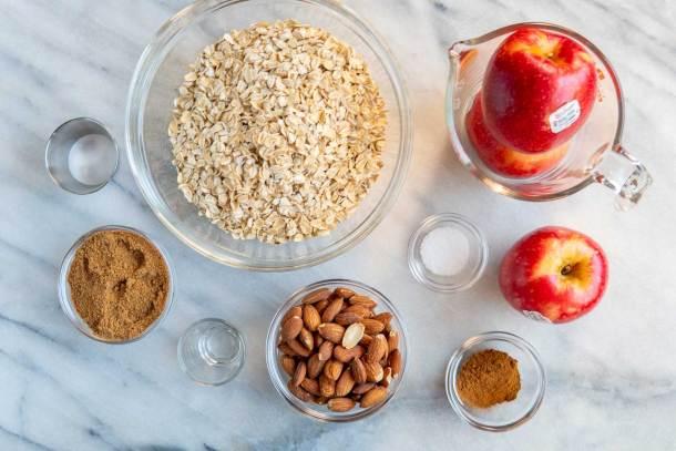 overhead image of ingredients for apple cinnamon almond blender muffins - oats, pples, almonds, cinnamon, baking soda, salt, sugar, almond extract