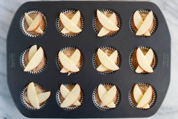 apple slices laid in x shape over muffin batter