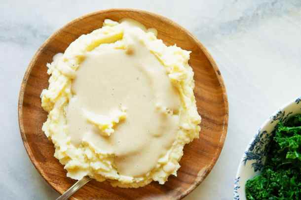 vegan mashed potatoes on a plate topped with vegan white gravy