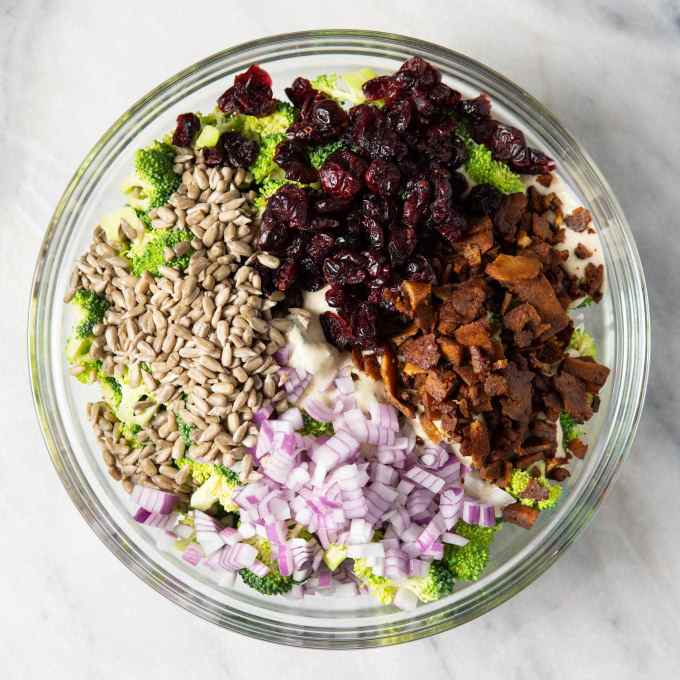 overhead shot of vegan broccoli salad ingredients in a glass bowl