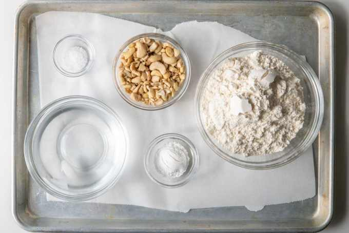 ingredients for oil-free vegan biscuits in glass bowls on a baking sheet