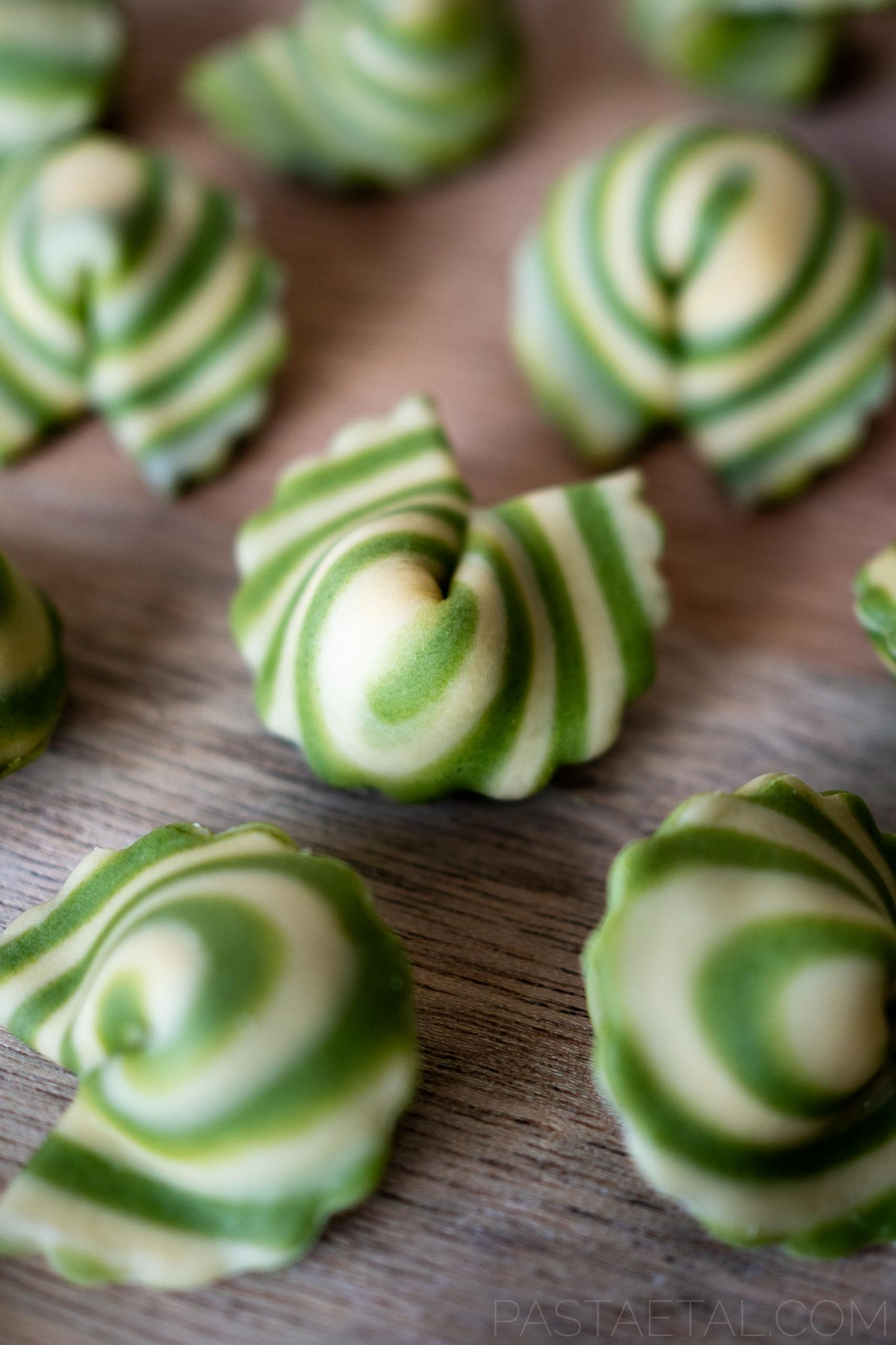 tilted close up of spinach spiralled cappellacci filled with asparagus and mascarpone on a chopping board