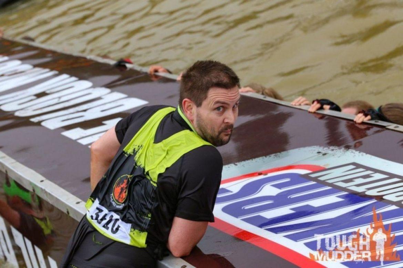 Partecipante che cerca di superare un ostacolo della Tough Mudder, foto Tough Mudder UK