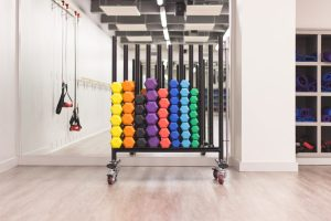 A rack of multi-colored dumbell exercise weights.