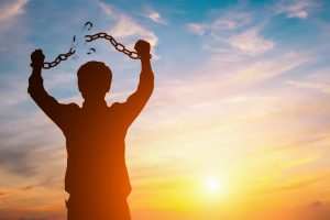 Silhouette image of a man with broken chains in sunset.