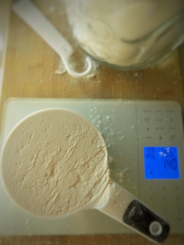 Flour in a measuring cup over gram scale