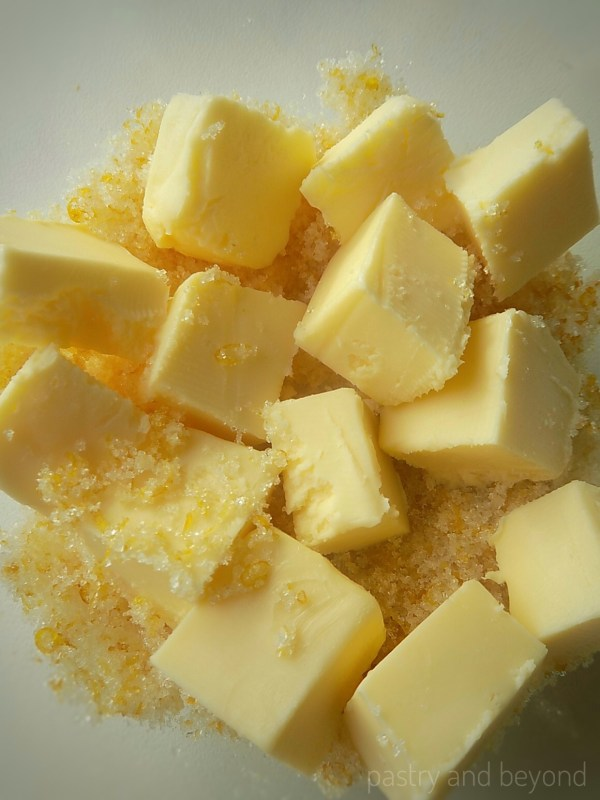 Cubed butter, lemon zest and sugar in a bowl.